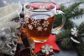 Na obrazku, stół, szklaną herbaty. Szklanka pokryta białymi gwiazdkami, stylizowanymi na gwiazdy ze śaniego. Na stole gałązka świerku i czerowna gwiazda, na której stoi szklanka z herbatą.